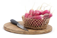 Fresh radishes in the woven basket with kitchen knife.  Royalty Free Stock Photos