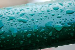 Detail of rain drops on green, close up. Fresh rain has fallen and left behind a beautiful formation of water drops on green plastic fence Royalty Free Stock Photos