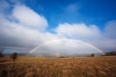 Fresh Rainbow in Prairie. Wide rainbow over wet prairie with hills in background Royalty Free Stock Photo