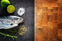 Fresh rainbow trout with lime and seasoning. Fish at dark background. Detail of preparation. Fresh rainbow trout near cutting board with lime and seasoning. Fish Stock Images