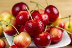 Fresh Rainier Cherries. Closeup horizontal photo of Rainier cherries, with water drops, in white dish on natural bamboo board Royalty Free Stock Photo