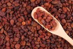Fresh raisins in a wooden spoon. Background of fresh raisins Stock Photo