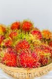 Rambutan on white table. Fresh Rambutan in bamboo basket on wooden table background Royalty Free Stock Images