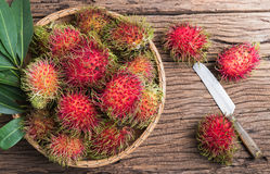 Fresh rambutan. In basket  on wood background Royalty Free Stock Photos