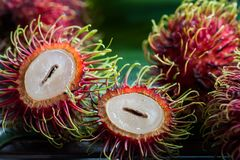 Fresh rambutan fruit and cross section showing the thick red skin and white flesh,. Delicious rambutan sweet fruit , closeup, fruit in Asia Stock Photos