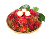 Fresh rambutan fruit with green leaves in bamboo basket Stock Image