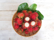 Fresh rambutan fruit with green leaves in bamboo basket. On wooden table, top view Royalty Free Stock Photos