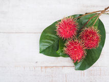 Fresh rambutan fruit with green leaves. On wooden table, top view Royalty Free Stock Photography