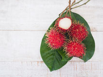 Fresh rambutan fruit with green leaves. On wooden table, top view Stock Photography