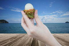 Fresh Rambutan fruit in woman hand holding peeled rambutan with a perspective wooden table over blurred sea and blue sky Stock Photos