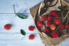 Fresh Rambutan Fruits. On old wood Stock Photo