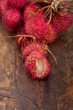 Fresh rambutan fruits. Fresh tropical rambutan fruits over rustic wood table Stock Photo