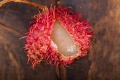 Fresh rambutan fruits. Fresh tropical rambutan fruits over rustic wood table Stock Photography