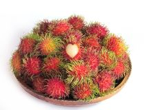 Fresh rambutan paste full of wooden trays. There is a pile in th. E front and a heart-shaped peeled rambutan to show off the meat on a white background Stock Image