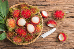 Fresh rambutan. In basket  on wood background Stock Photos