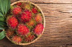 Fresh rambutan. In basket  on wood background Stock Images