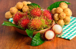 Fresh rambutan and wollongong on wooden background.  Royalty Free Stock Photo