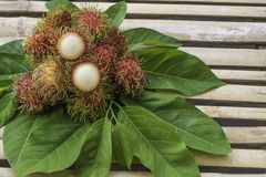 Fresh rambutan on wood background. Rambutan sweet delicious fruit.background of fresh Thai rambutans. rambutan pattern on wood background Stock Image