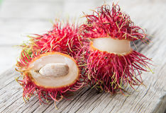 Fresh rambutan on wood texture. Background Stock Image