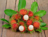 Fresh rambutan on wooden background. Fresh rambutan on a wooden background Stock Photo