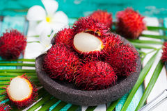 Fresh rambutans in a bowl on wooden background. Fresh rambutans in a grey stone bowl on wooden colorful background Royalty Free Stock Photos