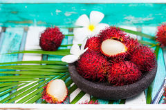 Fresh rambutans in a bowl on wooden background. Fresh rambutans in a grey stone bowl on wooden colorful background Royalty Free Stock Photo