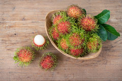 Fresh rambutans. On wood background Stock Photos