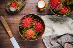 Fresh rambutans in a woodean bowl. On wooden background Stock Photo