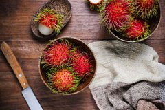 Fresh rambutans in a woodean bowl. On wooden background Royalty Free Stock Images
