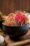 Fresh rambutans in a woodean bowl on wooden background. Close up Fresh rambutans in a woodean bowl on wooden background Stock Photography