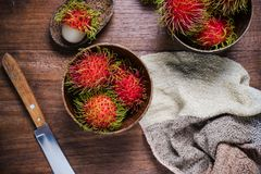 Fresh rambutans in a woodean bowl on wooden background. Fresh rambutans fruit in a woodean bowl on wooden background Stock Images