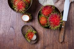 Fresh rambutans in a woodean bowl on wooden background. Top view Royalty Free Stock Photos