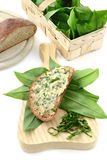 Fresh ramson butter on slice of bread. In background basket with ramson leaves Stock Photo