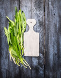 Fresh ramson on white cutting board and blue wooden background, top view, copy space Royalty Free Stock Image