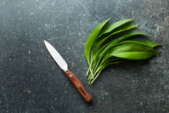 Fresh ramsons leaves. Wild garlic leaves and knife on old kitchen table. Top view Stock Photo