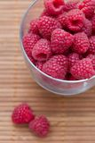 Fresh raspberries. In a glass on a bamboo mat Stock Image