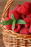 Fresh raspberries. Fresh sweet raspberries with water drops in a wicker basket close-up Stock Image