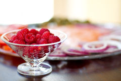 Fresh Raspberries. In front of a fresh Lox, onion tomato Plate Stock Photo