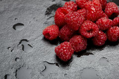 Fresh raspberries. On a wet and black kitchen surface Royalty Free Stock Photos