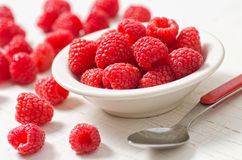 Fresh Raspberries. A small bowl of fresh raspberries against a rustic white background stock images