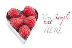 Fresh raspberries. In a heart isolated on white Royalty Free Stock Image