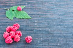 Fresh raspberries background. Heap of fresh raspberries and a leaf  on the table Royalty Free Stock Photography