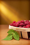 Fresh raspberries in the basket. On yellow background Royalty Free Stock Photo