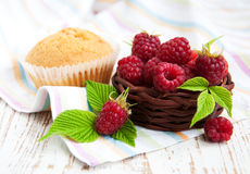 Fresh raspberries in the basket. And cupcake on a wooden  background Stock Photo
