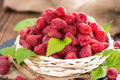 Fresh Raspberries in a basket. Small basket with fresh harvested Raspberries on wooden background Stock Photo