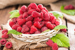 Fresh Raspberries in a basket. Small basket with fresh harvested Raspberries on wooden background Stock Images