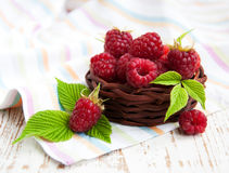 Fresh raspberries in the basket. On a wooden  background Royalty Free Stock Photo