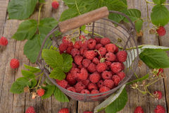Fresh raspberries in a basket. On a wooden background Stock Photo