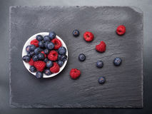 Fresh raspberries  and bilberry berries. Scattered on black background.Top view Royalty Free Stock Photo