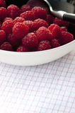Fresh raspberries in black bowl. With teaspoon Royalty Free Stock Photos